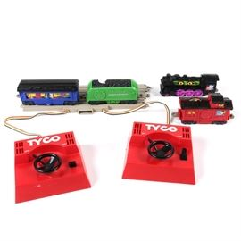 Children's Train Set Toys: A collection of plastic children's toy train elements. Features an engine, coal tender, car, and caboose from Lionel's Eerie Express train in a variety of colors. Also includes a piece of tan plastic track along with two Tyco wheel controllers.