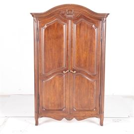 "Vintage Armoire by Davis Cabinet Company: A vintage armoire by Davis Cabinet Company. This piece features a curved crest rail and applied central motif of urn and flowers. The armoire includes two full length doors with raised panels and brass tone handles opening to an open storage space and four stacked drawers. The scalloped apron features a shell motif joining curved legs. It is marked ""David Cabinet Company"" to a drawer interior."