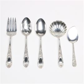 "S. Kirk & Son ""Rose"" and ""Repoussé"" Sterling Silver Serving Utensils: A five-piece collection of sterling silver serving utensils by S. Kirk & Son of Baltimore, MD (active 1846-1979). This include a meat fork, a pierced tablespoon, a solid tablespoon, and a shell casserole spoon in the Martin L. Millspaugh designed Rose pattern, first introduced in 1937, which features rose and leaf accented handles. They are presented with a jelly server in the Repoussé pattern, and each is marked to the back ""S. Kirk & Son Sterling"". The total approximate weight is 11.245 ozt."