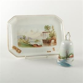 "Hand Painted Porcelain Bell and Dish: A porcelain bell and dish. Both pieces are composed of porcelain and feature gold tone trims. The dish features chamfered corners and both offer a landscape depiction across the exterior. The bell is marked ""1985"""