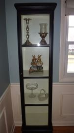 Lovely black glass display cabinet in beautiful condition.   Collectibles inside.