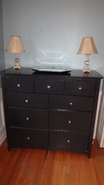 Lovely black clean dresser with small lamps.