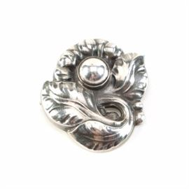 Georg Jensen Sterling Silver Floral Brooch: A Georg Jensen sterling silver brooch. This hollow brooch is stylized as a flower with scrolling leaf accents.
