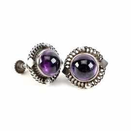 Georg Jensen Sterling Silver Amethyst Earrings: A pair of Georg Jensen sterling silver amethyst earrings. This pair of earrings features a central amethyst gemstone housed within a pierced bezel setting. The earrings are affixed to screw back ear wires.