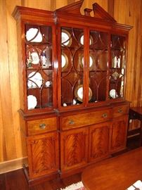 Handsome semi-antique  Kittenger mahogany breakfront secretary  with bubble glass doors, brass pulls and open pediment