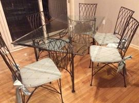 Vintage wrought iron patio set. Glass top table, 5 chairs and 2 bar stools that match