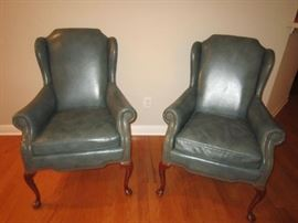 pair of blue grey leather wing chairs