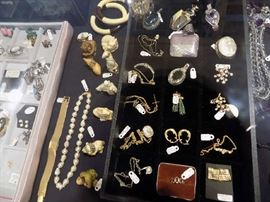 Assorted gold and silver jewelry priced less than $100. Six ivory netsukes at left are reduced 50%.