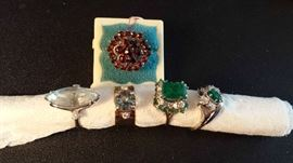 Left to right: Light blue topaz, diamond and medium color blue topaz, emerald and diamond, emerald and diamond, garnet cluster in back.