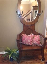 Antique hall tree with seat storage and oval mirror