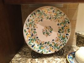 """Round 16"""" D ivory platter with center design of yellow birds, wide band of yellow birds, flowers,  foliage in yellow, blue, and green around rim, black iron easel with scroll legs to hold platter"""
