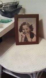 Shirley Temple framed photo on wicker table