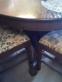Round oak table and chairs.  Note claw feet