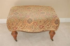 Tan fabric Ottoman with wood legs and wheels