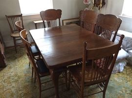 Antique oak dining table with 6 pressed back chairs. Some with cane bottoms, some covered.
