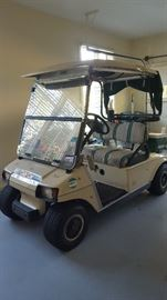 Club Golf Cart with New Batteries Stored Under Cover.