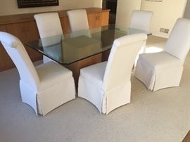 "12. Glass Topped Dining Table w/ Two Oak Wood Bases (40"" x 78"" x 30"")                                                               13. 6 Parsons Dining Chairs Covered in Cream Canvas (20"" x 24"" x 41"")"