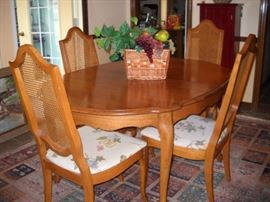 WALNUT DINING TABLE AND CANE BACK CHAIRS