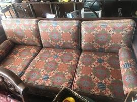 Couch with damaged caning and Aztec cushions