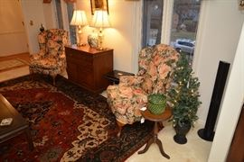 pair floral wingback chair, lighted Christmas trees, part of Panasonic surround sound, rug