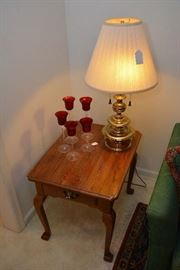 single drawer table, single brass lamp, candle holders