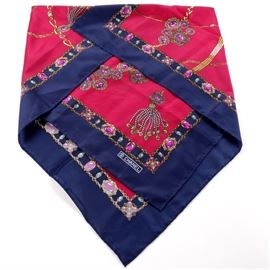 "Chanel Silk Scarf: A Chanel silk scarf. This scarf features a red field with a jewel motif in pink, light blue, gold, and gray, with a navy border. The scarf is finished with a hand rolled edge, and is printed ""Chanel"" to the corner in white."