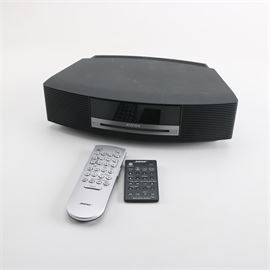 Bose Wave Music System: A Bose Wave music system, in black. The system features alarm clock, AM/FM radio, CD, and AUX functions with an included remote control and user's manual. An affixed manufacturer's label notes model number AWRCC1 and serial number 033975C80677574AC.