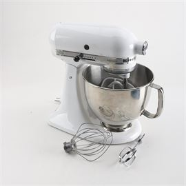 "KitchenAid ""Artisan"" Stand Mixer and Accessories: A KitchenAid Artisan stand mixer and accessories. This white KitchenAid Artisan tilt head stand mixer features ten speeds with stainless steel mixing bowl with handle. Accessories included dough hook, beaters and paddle beater, flour shield and instruction and recipe booklet."