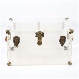 Clear Acrylic Trunk: A clear acrylic trunk. This steamer trunk has a clear acrylic body with brass hardware, including latches and a strap lock to the front, corner brackets, tan leather handles on the sides, strap hinges to the back, and chains to the inside.