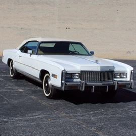 White Cadillac El Dorado Convertible: A 1976 white Cadillac El Dorado; VIN is 6L67S6Q219349 and mileage is 33518. This white full sized coupe Fleetwood 2-door automobile features seating for six, has a 3-speed automatic transmission, front wheel drive, automatic level control rear suspension, radial tires with branded hubcaps, Cotillion white paint with chrome grill and logo, beige leather interior with padded seat and woodgrain accents on the dashboard. Car also features power windows and locks, ash receivers, AM/FM radio, chrome trim and rag top. Included are a 1976 shop manual, logo key-ring and 1976 owner's manual.