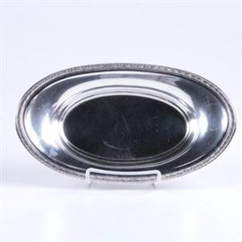 """International Silver Co. Anthemion Rimmed Sterling Silver Bread Tray: A sterling silver bread tray by International Silver Co. This tray features an oval form with upturned sides and a raised anthemion rim. It is marked """"International Sterling J50"""" to the underside and the approximate weight is 7.725 ozt."""