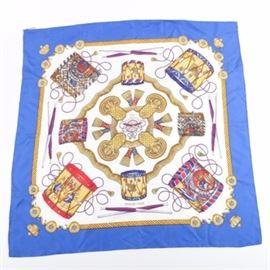 """Hermès """"Les Tambours"""" Silk Scarf: A Hermès Les Tambours scarf. The silk scarf designed by Joachim Metz features a military drum corp motif with tassels, drums patterns and sticks in red, blue, gold, tan and white. The edges are rolled and hand-stitched, and the scarf still retains the original fabric tag."""