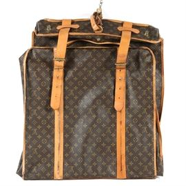 "Louis Vuitton Garment Bag: A Louis Vuitton garment bag. The bag features a fold-over, handled design with the signature monogrammed brown leather exterior framed in cognac leather with yellow stitching. The bag also features brass toned metal hardware and is marked, 'Made in France by Louis Vuitton"" to the interior."