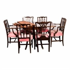 Hepplewhite Style Drop-Leaf Dining Table with Six Assembled Chairs: A Hepplewhite style, drop-leaf dining table with three leaves, on three trestle supports with fluted turned pedestals and splayed legs, having brass-tone feet. The two arm and two side chairs, each have have a tablet crest rail, above three pierced splats and square front legs with spade feet. Two additional Chippendale style side chairs have been assembled, all having rose upholstered seats.