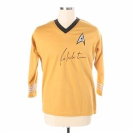 William Shatner Autographed Star Trek Shirt JSA COA: A Star Trek uniform shirt signed by William Shatner. This item is a gold shirt, similar to that worn by Shatner during his time as Captain Kirk from 1966-69. It is signed by Shatner to the front. A tag with authentication number WP447828 from JSA is attached to the shirt.