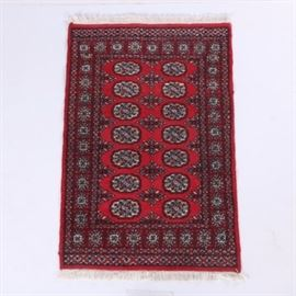 Hand-Knotted Pakistani Bokhara Accent Rug: A hand-knotted Pakistani Bokhara accent rug. This wool rug is rendered in a palette of scarlet, burgundy, peach, ivory, black, and slate blue. It begins with a vertical strip of Chemche-style guls flanked by two vertical rows of Tekke-style medallions, over a scarlet field. Framing the field are three wraparound geometric borders, including a main border featuring boxed starburst motifs. Two horizontal panels, one at the top, one at the bottom, each feature a diamond-lattice pattern. Selvedges are overcast, the rug finishing at each end with ivory cotton warp fringe. It is unlabeled.