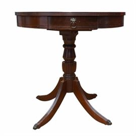 Federal or Duncan Phyfe Style Drum Table: A Federal or Duncan Phyfe style drum table in mahogany, having a round top with reeded edge, above a deep apron with one drawer, having a lion mask and ring pull. Mounted on a turned and reeded pedestal, the base has four splayed legs, terminating into brass paw feet. Circa 1940s.