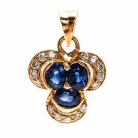 18K Yellow Gold Sapphire and Diamond Pendant: An 18K yellow gold sapphire and diamond pendant. This pendant features three oval faceted sapphires surrounded by fifteen round brilliant cut diamonds in a yellow gold clover shaped pendant.
