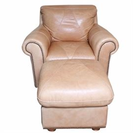 Leather Club Chair with Ottoman: A leather club chair with ottoman. The chair features a cushioned back with rolled arms, cushioned seat and apron front on bun feet. The chair is upholstered in a nude tone leather and includes patchwork piecing and nailhead trim. Also included is a coordinating ottoman with the same patchwork pieced leather cushion top, apron sides, nailhead trim and bun feet.