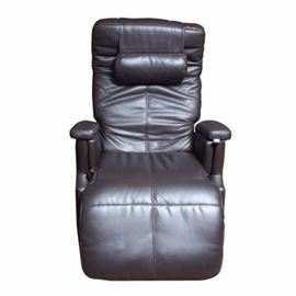 Leather Recliner: A leather recliner. This dark leather recliner features a high back with a head pillow and cushioned back joining curved armrests flanking a cushion seat with rising footrest. There are no visible maker's marks.