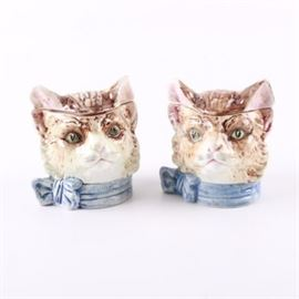 Vintage Ceramic Cat Head Humidors: A pair of vintage ceramic humidors. Each tobacco jar depicts a cat with a blue ribbon and bow around its neck. The jars have a brown, white, green, black, and blue glaze finish. There are no visible makers marks.