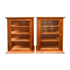 Two Small Wood Display Cases: A pair of wood display cases. Each case has a magnetic glass door that open up to four shelves.The sides feature rectangular windows. The back of each case has two wall mounting brackets.