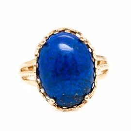 10K Yellow Gold Lapis Lazuli Ring: A 10K yellow gold lapis lazuli ring. This ring showcases a center lapis lazuli held in a scalloped setting mounted atop split shoulders with rope accents.