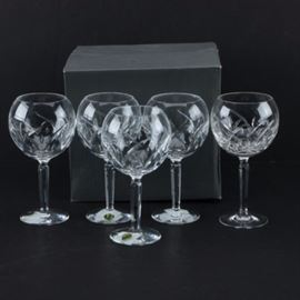"Waterford ""Lucerne"" Crystal Balloon Wine Glasses: A set of Waterford Lucerene crystal balloon wine glasses. Each glass displays a curved, crisscross line pattern to the bowl and a beveled stem. The pieces are etched ""Waterford"" to the base and come with the original box."