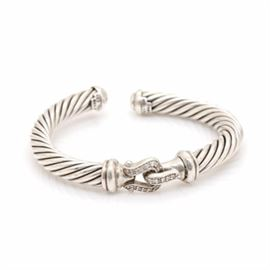 "David Yurman Sterling Silver Diamond ""Cable"" Cuff Bracelet: A David Yurman sterling silver 0.23 ctw diamond cuff bracelet from the Cable collection. This bracelet features a center diamond set buckle with David Yurman's classic cable design decorating each side of the cuff."