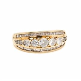 10K Yellow Gold Diamond Ring: A 10K yellow gold 0.75 ctw diamond ring. This ring features a center row of round diamonds raised between two channels of baguette diamonds.