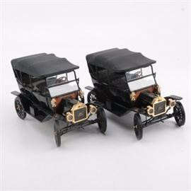 "Pair of 1920s Ford Model T Touring Cars: A pair 1920s Ford Model T Touring car. This pair of scale replica cars depict 1920s Ford Model T Tourings and are painted black with gold tone metal accents. The cars include functional hoods to the front and are marked ""Ford""."