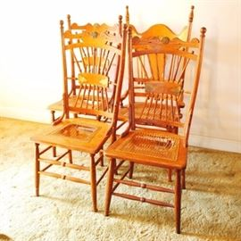 Walnut and Oak Dining Chairs: A group of four walnut and oak chairs. They have curved, decorated top rails over turned spindles gathered in the center with a horizontal splat. They have cane seats, and tapered and turned legs joined by double box stretchers. One is an arm chair with a different design to the back rest; it has tall finials, bead accents, and a vase-shaped center splat flanked by straight spindles.