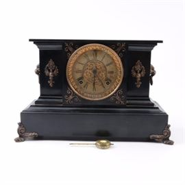Vintage Ansonia Wood Mantel Clock: A vintage Ansonia wood mantel clock. The clock has a wood case with a black finish and lion head side handles. The clock has a brass bezel and glass cover that displays a gold-tone embossed bezel surrounding a white face with more decorative raised scrollwork on the center, black Roman numerals and hands with two key arbors. Other features of the clock include a brass pendulum, an eight-day strike and chime mechanism and the clock stands on a plinth style base with brass scrolled feet.