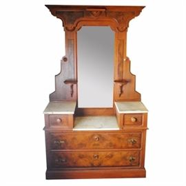 Antique Renaissance Revival Walnut Dropwell Dresser: An antique Renaissance Revival walnut dropwell dresser. This American three piece white marble top dropwell dresser is made of walnut with burl walnut veneer, having an architectural pediment with raised burl panels and applied turned demi-roundels over and around the frame of the rectangular mirror with flanking candle shelves at the base; over two marble top handkerchief boxes, the drawer fronts with raised burl veneer panels and a lower marble top in between; over a pair of long drawers, one over the other, each with a turned round escutcheon and a pair of brass plates with ring pulls; the case resting on a raised plinth. Drawers made with Knapp joints used 1871-1900. No key. No apparent maker's mark.